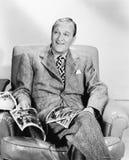 Man sitting on an armchair reading a magazine Stock Photo