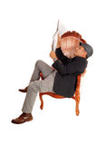 Man sitting in armchair reading paper. Royalty Free Stock Photos