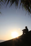 Man sitting as silhouette by the sea Stock Photos