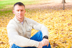 Man Sitting on Autumn Leaves Stock Images