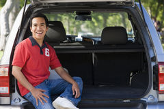 Man sitting in back of van smiling Stock Image