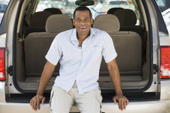 Man sitting in back of van smiling Royalty Free Stock Images