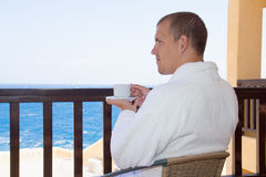 Man sitting on balcony with cup of coffee Stock Image