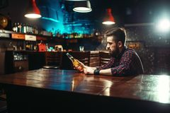 Man sitting at the bar counter, alcohol addiction. Sad man sitting at the bar counter and holds the bottle with alcohol beverage in hands. Male person in pub stock images