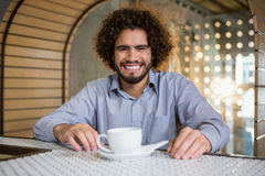 Man sitting on bar counter with cup of tea Royalty Free Stock Photography