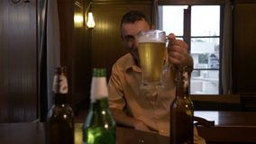 Man sitting at a bar with a glass of beer in front and cheers and drinks -. Man sitting at a bar with a glass of beer in front and cheers and drinks stock video footage