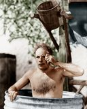 Man sitting in a barrel taking a bath and looking through his monocle Stock Image
