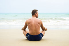 Man sitting on beach. Mature man sitting crosslegged on a sandy beach and meditating or just relaxing and thinking Royalty Free Stock Photo