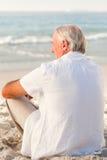 Man sitting on the beach Stock Photos