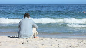 Man sitting at beach Stock Photos
