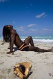 Man sitting on the beach in cuba. Black man sitting on the beach with coquilage over blue sea and blue sky Royalty Free Stock Images
