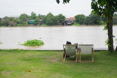 Man sitting on beach deck chairs in the grass. With river, relax concept Royalty Free Stock Image