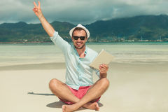 Man sitting on the beach with ipad in hand showing victory sign. Young man sitting on the beach with ipad in one hand and with the other hand showing victory Royalty Free Stock Photos