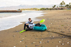 Man sitting on the beach with kayak. Traveling by sea. Leisure activities on the water. Royalty Free Stock Images
