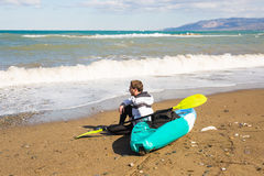 Man sitting on the beach with kayak. Traveling by sea. Leisure activities on the water. Stock Photography