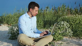 Man sitting on beach with a laptop. Freelance stock video footage