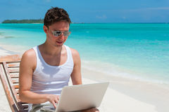 Man sitting at the beach with laptop Royalty Free Stock Image