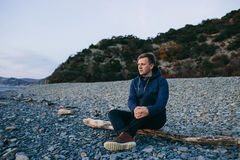 Man sitting on the beach and looking forward. Close up of man sitting on the beach and looking forward Stock Photos