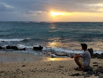 Man Sitting by the Beach Looking at Setting Sun royalty free stock photography