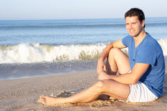 Man sitting on beach relaxing Royalty Free Stock Image