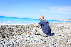 Man Sitting On Beach, Texting On His Phone Stock Image