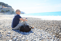 Man Sitting On Beach, Texting On His Phone Stock Images