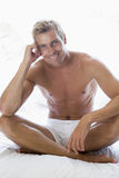 Man sitting on bed Royalty Free Stock Photos