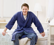 Man sitting on bed in bathrobe Stock Image