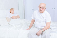 Man sitting on the bed. Disappointment. Sad senior men sitting on bed and looking away with his wife in background Stock Photo