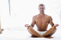 Man sitting on bed doing yoga