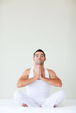 Man sitting on bed doing yoga with copy-space Stock Image