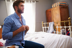Man Sitting On Bed Getting Dressed In Morning Stock Image
