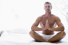 Man sitting on bed meditating Stock Photography