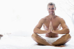 Man sitting on bed meditating Royalty Free Stock Image