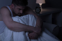Man sitting in the bed. At night Stock Photos