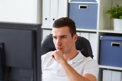 Man sitting behind the monitor in the office Stock Photography