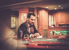 Man sitting behind poker table Royalty Free Stock Photos