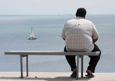 A man sitting on the bench. And looking at the sea Stock Photo