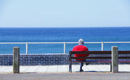 Man sitting on bench. Elderly man looking out to sea sitting on a bench Stock Image