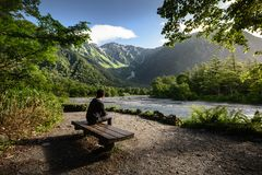 Man sitting on bench alone in Kamikochi national park Royalty Free Stock Photography