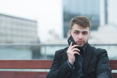 A man sitting on a bench in the background of a city landscape and talking on the phone. Stock Images