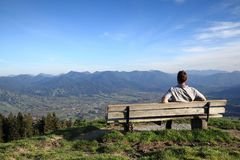 Man is sitting on a bench. In the bavarian alps Royalty Free Stock Image