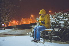 Man sitting on a bench in cold winter night. Frozen Royalty Free Stock Photography