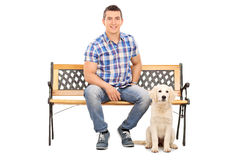 Man sitting on a bench with a cute puppy Royalty Free Stock Photography
