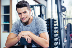 Man sitting on the bench with dumbbells at gym Royalty Free Stock Image