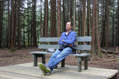 Man Sitting on a Bench with Eyes Closed in the Forest Royalty Free Stock Image