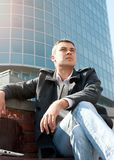 Man sitting on a bench in front of a building Stock Images