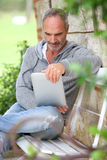 Man sitting on bench in garden reading ebook Royalty Free Stock Images