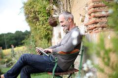 Man sitting on bench in garden. Man spending week-end in countryside Royalty Free Stock Image