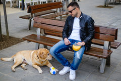 Man sitting on the bench with his dog lying on the ground Stock Photography